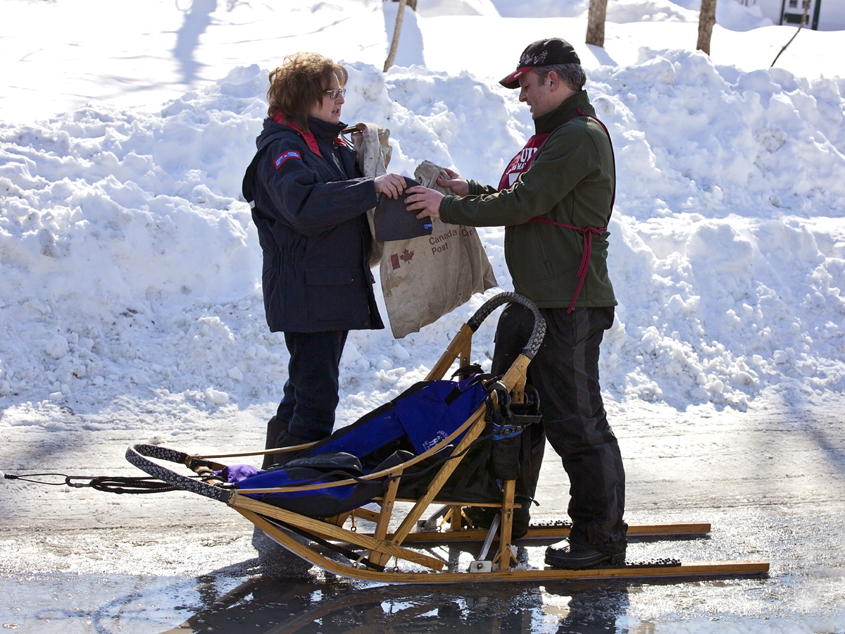 Annual Seguin Sled Dog Mail Run musher handing over the mailbag